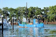 Ein blaues Fischereiboot / Kutter verlässt am frühen Morgen den Hafen von Lauterbach und fährt Richtung Greifswalder Bodden.