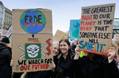 Pappschilder  mit der Aufschrift: ERDE - we march for our future und The greatest Threat to our Planet is the Belief that someone else will save it.   Fast 10 000 SchülerInnen protestieren am 15.03.2019 bei der Fridays for Future-Demonstration in H