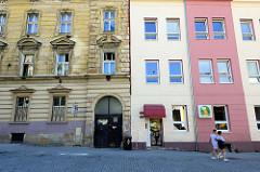 Wohnhäuser in unterschiedlichem baulichem Zustand. Leerstehendes Gründerzeit-Etagenhaus mit verfallener Fassade, daneben ein schlichter Wohnblock mit glatter Putzfassade.