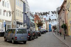 Alte Schuhe hängen am Drahtseil der ehem. Straßenbahn, das sich über die Norderstraße in Flensburg spannt. Warum begonnen wurde, die alten Schuhe in das Seil hochzuwerfen ist unklar.