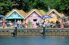Mit reetgedeckte bunte Verkaufspavillions an der Hafenspitze / Hafenpromenade in Flensburg.