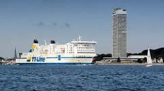 Das Fährschiff Nils Holgersson verlässt auf der Trave das Lübecker Terminal und fährt auf der Höhe Travemündes in die Ostsee ein - re. das 1974 errichtete Hochhaus Hotel Maritim.