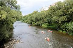 Kanus fahren auf der Eger / Ohře in Karlsbad /  Karlovy Vary. Die Ufer sind mit Sträuchern und Bäumen bewachsen - dahinter sind Hochhäuser der Stadt zu erkennen.