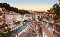 Historische, kolorierte Fotografie vom Zentrum Karlsbad - Blick über den Fluß Teplá zu Wohnhäusern / Geschäfthäuser, Glasfabrik im Zentrum des Ortes - re. im Vordergrund die Mühlbrunncolonnaden.