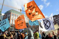 Fahnen mit der Aufschrift: Jetzt handeln + Klimawandel = Massenmord. Fast 10 000 SchülerInnen protestieren am 15.03.2019 bei der Fridays for Future-Demonstration in Hamburg für mehr Klimaschutz