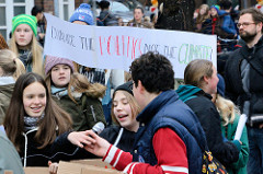 Fridays for Future - Demo in Hamburg - 01.03.2019. DemonstrantInnen auf dem Gänsemarkt tragen ein  Transparent mit der Forderung: Chance the Politics not the Climate!
