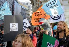 Schilder und Fahnen u.a. mit der Aufschrift Klimawandel = Massenmord. Fast 10 000 SchülerInnen protestieren am 15.03.2019 bei der Fridays for Future-Demonstration in Hamburg für mehr Klimaschutz.