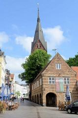 Historische Architektur in Flensburg - rechts der 1595 errichtete Schrangen in der Altstadt - früher Nutzung für Verkaufsstände von Bäcker und Schlachter. Im Hintergrund der Kirchturm der Sankt Marienkirche.