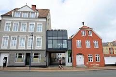 Alte Bebauung an der Straße Schiffbrücke in Flensburg - Torüberbauung mit einem modernen Glaswürfel.