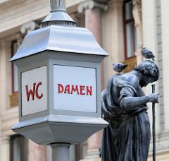Lampe, Hinweis WC Damen am Graben in der historischen Innenstadt von Wien - im Hintergrund die Bleistatue vom Josefsbrunnen - Darstellung des Heiligen Joseph.