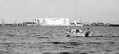 Ein Segelboot fährt mit Motorkraft auf dem Strelasund Richtung Stralsund;  im Hintergrund die Rügenbrücke und die Werfthalle der MV Werften.