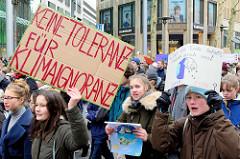 Fridays for Future - Demo in Hamburg - 01.03.2019. DemonstrantInnen tragen Demoschilder mit den Forderungen / Slogans: Keine Toleranz für Klimaignoranz - Was die Erde befällt, befällt auch uns.