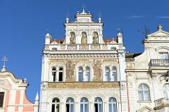 Giebel eines Wohn- und Geschäftshauses am Platz der Republik / náměstí Republiky in der denkmalgeschützten Altstadt von Pilsen / Plzeň.  Aufwändige Fassadenmalerei mit Jahreszahl 1894 - Skulpturen in Muschelnischen.