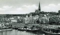 Altes Bild vom Flensburger Hafen - Frachtschiffe am Kai, Eisenbahnwaggons. Im Hintergrund die St. Jürgenkirche auf dem Jürgensbyer Hügel.