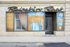 Leerstehendes Reisebüro mit Neonschrift - Fassadenschild; Architektur in der Penzinger Straße von Wien.