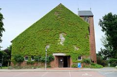 Mit Rankpflanzen bewachsene Gebäudefront der Christuskirche in Flensburg Mürwik - geweiht 1958, Architekten Bernhard Hopp und Rudolf Jäger.