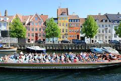 Blick über den Christianshavns Kanal in Kopenhagen. Ein vollbesetztes Touristenschiff fährt durch den Kanal.
