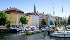 Blick über den Christianshavns Kanal in Kopenhagen. Ein vollbesetztes Touristenschiff fährt durch den Kanal an dessen Kaimauer unterschiedliche Boote festgemacht haben - im Hintergrund der Kirchturm der Vor Freisers Kirke / Erlöserkirche.