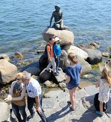 Touristen fotografieren sich und die Kleinen Meerjungfrau an der Uferpromenade Langelinie in Kopenhagen. Bronzefigur nach dem Vorbild in dem gleichnamigen Märchen des dänischen Dichters Hans Christian Andersen; Bildhauer Bildhauer Edvard Eriksen, 191