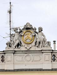 Detailbilder der Architektur Wiens - Dachrelief mit Putten und goldenem Monogramm.