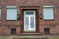 Bilder aus dem Hamburger Stadtteil Billbrook - Eingang eines Backsteingebäudes / Verwaltungsgebäude in der Berzeliusstraße, die Fenster sind mit Rollläden geschützt.