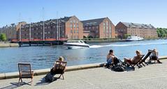 Kai an der Hafenpromenade von Kopenhagen laden zum Sitzen und sich Sonnen ein - am Ufer stehen alte Backstein-Lagerhäuser am Hammershøis Kaj.