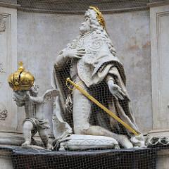 Detailbilder der Architektur Wiens - Skulptur Krönungszeremonie, eine Putte / Engelwesen mit Flügeln hält die REichskrone.