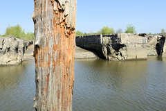 Fotos vom Hamburger Stadtteil Finkenwerder, Bezirk Hamburg Mitte - Blick über den Rüschenkanal zu den gesprengten Fink II U-Boot Bunkern die früher als Teil der deutschen Werft jetzt unter Denkmalschutz stehen. Im Vordergrund ein verwitterter Holzdal