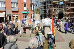 Ostermarsch 2019 - Demo für Abrüstung in Hamburg. Bänkelsänger mit politischen Antikriegsliedern - Bronzeskulpturen der Kreuzigungsgruppe vor der  Dreieinigkeitskirche von Hamburg St. Georg.