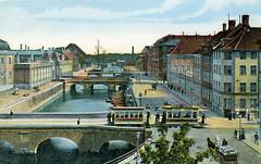 Koloriertes altes Foto vom Frederiksholms Kanal in Kopenhagen - eine Straßenbahn und ein Pferdefuhrwerk / Doppelgespann mit Ladung fahren auf der Straße; lks. der Eingang zum Schloss Christiansborg.