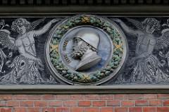 Detailbilder der Architektur Wiens - Erinnerungsmedaillon Reliefbüste Peter Fischer im Eichenkranz.