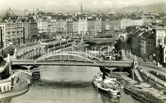 Historische Luftaufnahme vom Donaukanal in Wien - Panorama der Stadt; lks. der Franz Josefkai - ein Arbeitsboot und Fahrgastschiffe liegen am Kai - im Hintergrund ein Badeschiff.