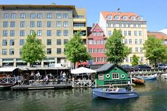 Moderne und historische Architektur am Ufer des Christianshavns Kanal in Kopenhagen. Auf dem Wasser ein Ponton als Café / Gaststätte - ein Mietboot fährt auf dem Kanal.