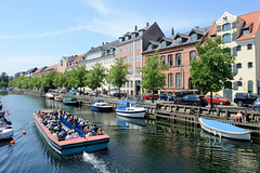 Ein Fahrgastschiff / Cabrio fährt mit Touristen an Bord auf seiner Rundfahrt durch Kopenhagen auf dem Christianshavns Kanal.