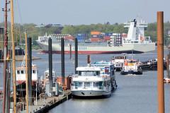 Fotos vom Hamburger Stadtteil Finkenwerder, Bezirk Hamburg Mitte - Arbeitsschiffe und Fähren liegen Steendiek-Kanal, auf der Elbe fährt ein Containerschiff elbabwärts.