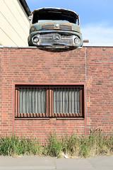 Bilder aus dem Hamburger Stadtteil Billbrook - Frontteil / Führerhaus eines alten Mercedes-Benz Lastwagen auf dem Hausdach eines Schrotthandels am Billbrookdeich.