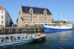Historisches Lagerhaus am Ufer des Kanal Nyhavn in Kopenhagen - ein Fahrgastschiff befördert Touristen über die Kanäle der Stadt.