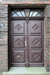 Bilder aus dem Hamburger Stadtteil Billbrook -  Holztür mit geschnitzter Füllung - Eingangstür eines denkmalgeschützten Verwaltungsgebäudes in der Moorfleeter Straße; errichtet 1923, Architekt von Halle.