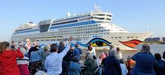 Das Kreuzfahrtschiff AidaLuna verlässt die Hansestadt Hamburg, Fahrgäste einer Hafenfähre winken dem auslaufenden Passagierschiff zu oder fotografieren das auffällige Schiff.