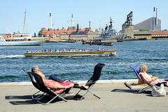Uferanlage im Kopenhagener Hafen - Menschen geniessen in Liegestühlen die Sonne und die Aussicht auf das Wasser - ein Fahrgastschiff / Cabrio fährt mit Touristen an Bord auf seiner Sightseeing Tour an der Promenade entlang.