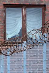 Bilder aus dem Hamburger Stadtteil Billbrook - Fenster mit Raffgardine und Metallzaun der mit NATO Stacheldraht abgesichert ist.