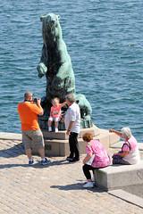 Statue eines aufrecht stehenden Bären im Hafen von Kopenhagen - Touristen fotografieren sich an der lebensgroßen Skulptur