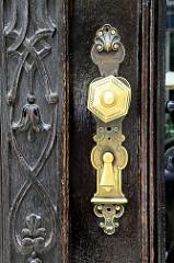 Jugendstilschnitzerei und Messing-Türschloss am Eingang vom Wohn- und Geschäftshaus des ehem. Herrenmodegeschäftes P. C. Leschka in der Spiegelgasse von Wien.