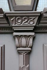 Bilder aus dem Hamburger Stadtteil Billbrook - Holztür mit geschnitzter Jahreszahl - Eingangstür eines denkmalgeschützten Verwaltungsgebäudes in der Moorfleeter Straße; errichtet 1923, Architekt von Halle.
