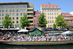Moderne und historische Architektur am Ufer des Christianshavns Kanal in Kopenhagen. Auf dem Wasser ein Ponton als Café / Gaststätte - ein dicht mit  Touristen besetztes Fahrgastschiff fährt auf seiner Kanal Tour durch die Kanäle der Stadt.