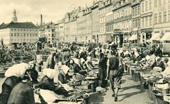 Historische Ansicht vom Fischmarkt in Kopenhagen - Frauen in Tracht verkaufen frische Fische aus Körben und Kisten - am Kanalufer liegen Fischerboote.