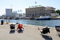 Uferanlage im Kopenhagener Hafen - Menschen geniessen in Liegestühlen die Sonne und die Aussicht auf den Nordre Toldbod