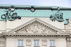 Detailbilder der Architektur Wiens - oxidiertes Kupferdach mit Skulpturen, Tympanon mit Reliefdarstellung.