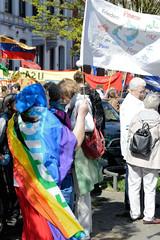 Ostermarsch 2019 - Demo für Abrüstung in Hamburg.  Eine Frau ist in die Regenbogenfahne Peace eingehüllt und schwngt eine weisse Fahne mit den Aufschriften Frieden in unterschiedlichen Sprachen.