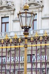 Detailbilder der Architektur Wiens - Hofburgzaun / Lampe, historischer Eisenzaun im Stil des Neo-Barocks - Entwurf von Moritz Löhr.